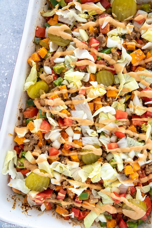 a white casserole dish with healthy BLT burger casserole drizzled with special sauce