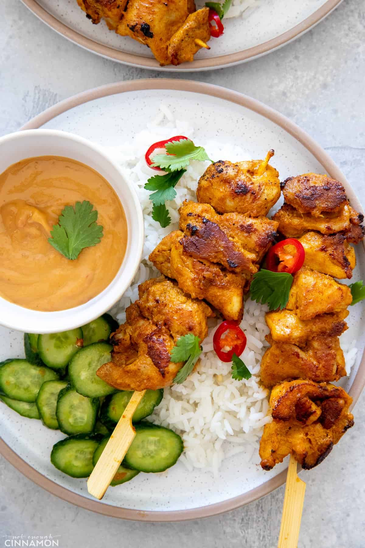 Satay Thai Chicken Skewers served with healthy satay sauce and a side of cucumber salad