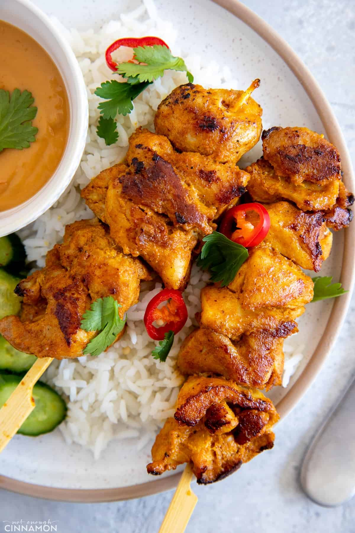 two juicy marinated Thai style chicken skewers served on a bed of rice with a side of peanut sauce