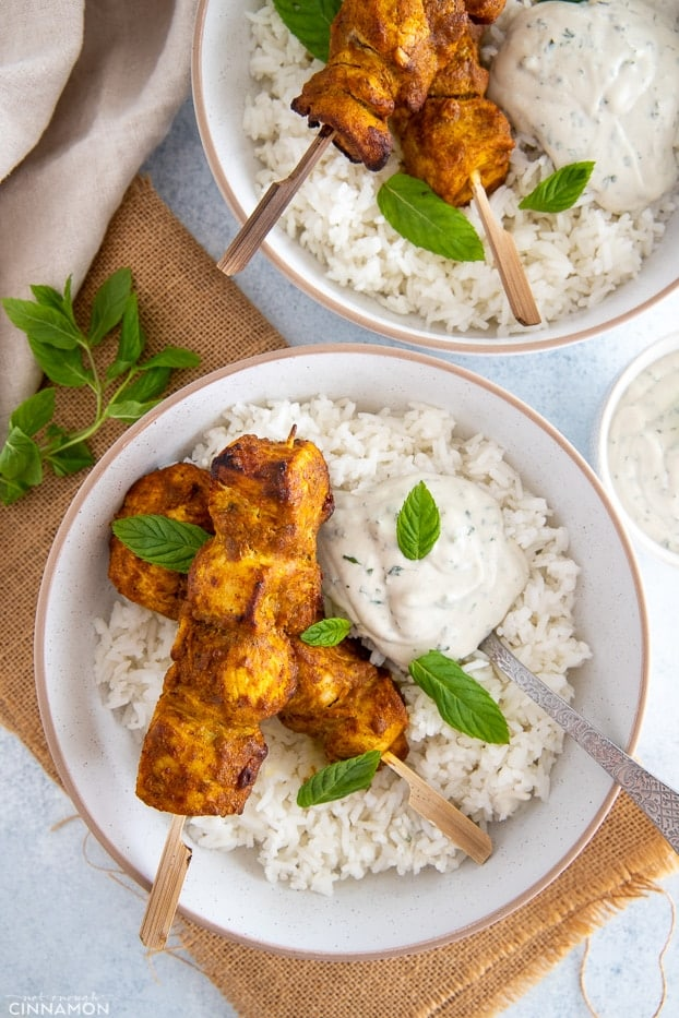overhead shot of two bowls filled with rice and topped with baked tandoori chicken skewers served with dairyfree yogurt dip