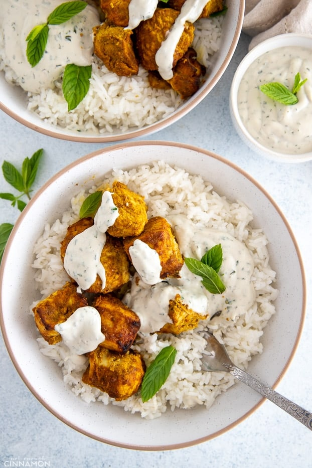 a bowl with rice topped with tandoori chicken and drizzled with yogurt dip