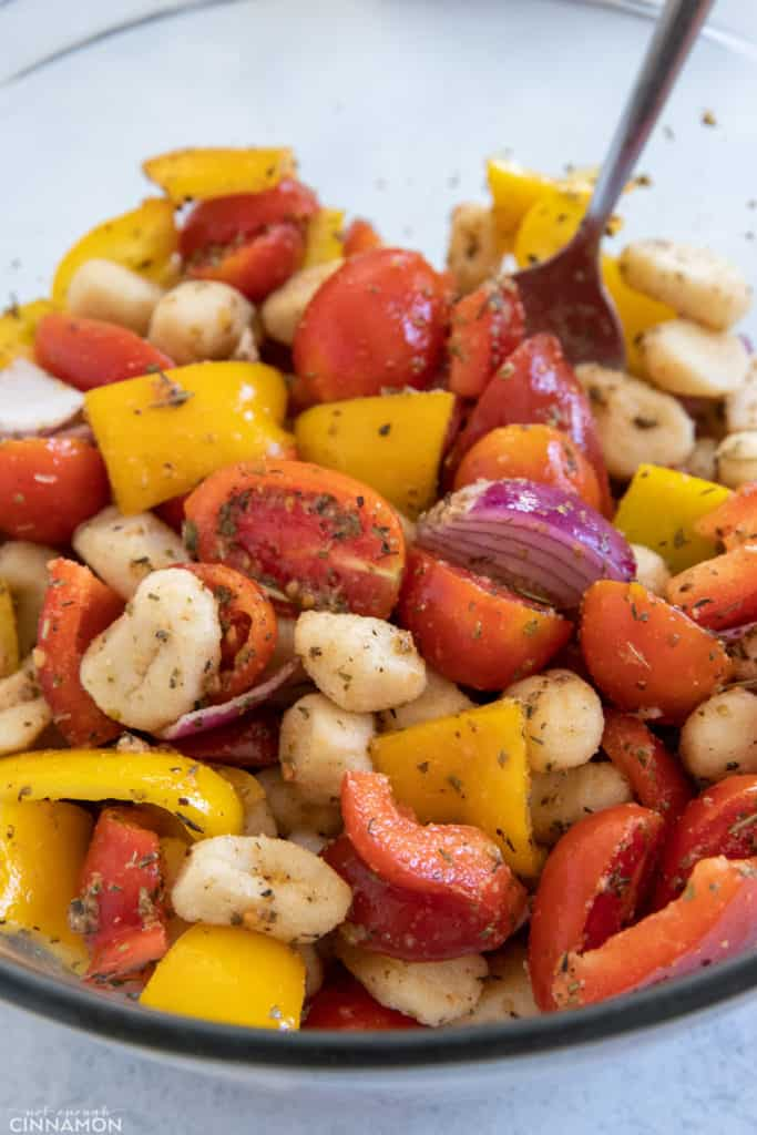 gnocchi, chopped bell pepper, onion, and tomatoes being tossed in a bowl with olive oil and herbs
