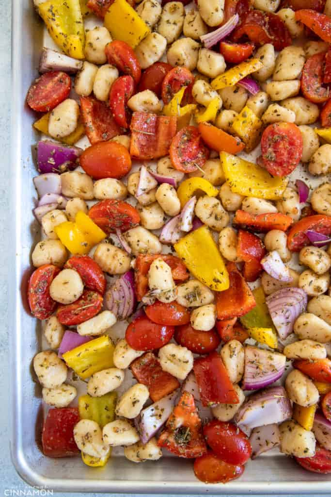 gnocchi and vegetables tossed with Italian herbs and olive oil being spread onto a baking sheet