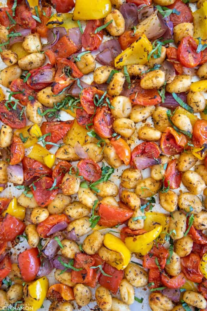 overhead shot of a sheet pan with crispy baked gnocchi and roasted vegetables sprinkled with fresh basil
