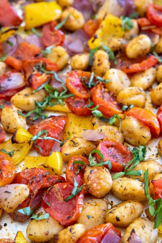 crispy baked gnocchi, cherry tomatoes and bell pepper on a sheet pan
