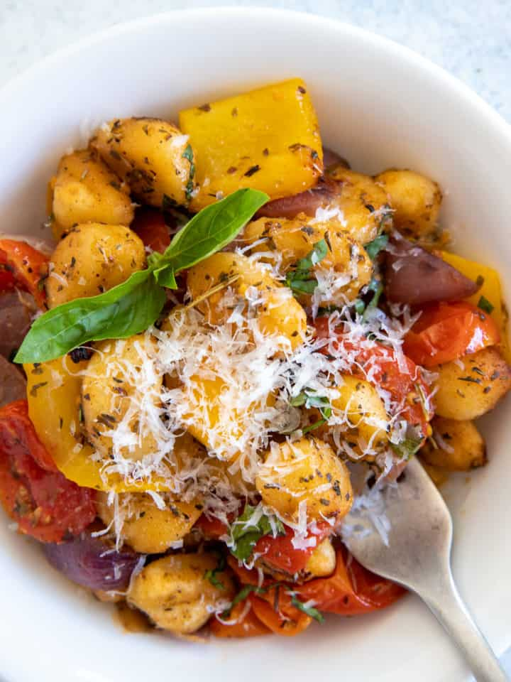 a small bowl with crispy sheet pan gnocchi with roasted vegetables served with grated parmesan and basil