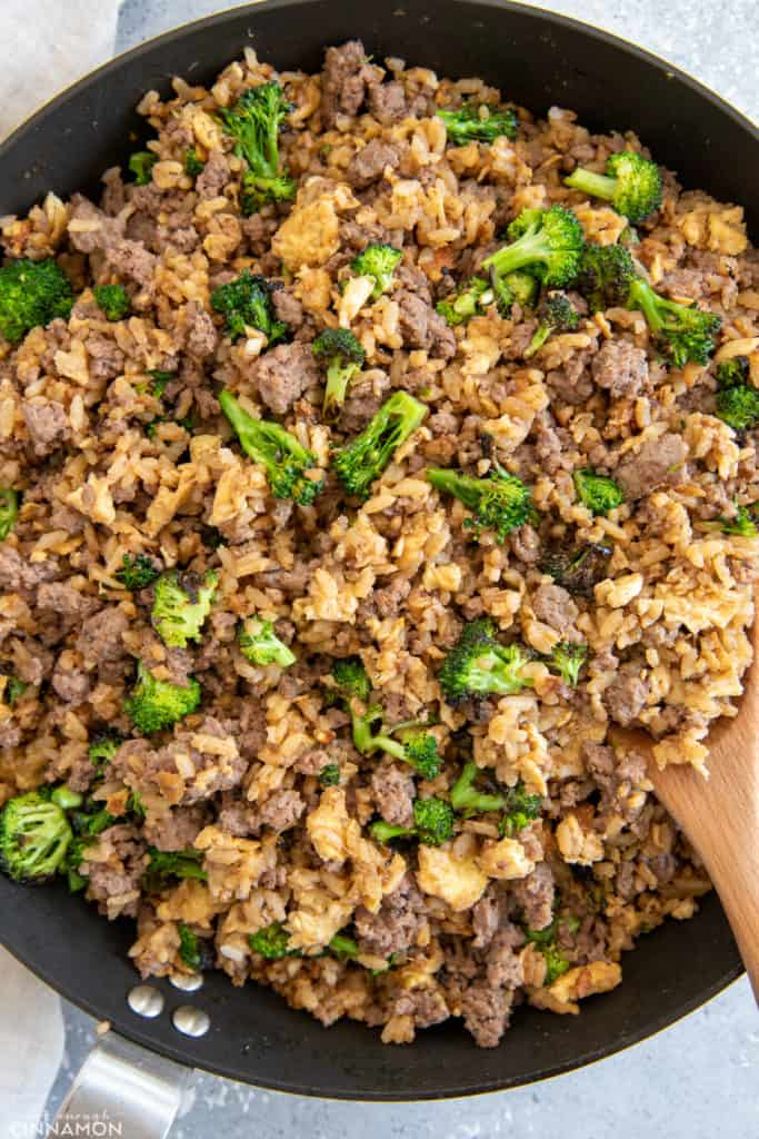 Healthy Asian Beef and Broccoli Fried Rice being stir-fried in a big skillet