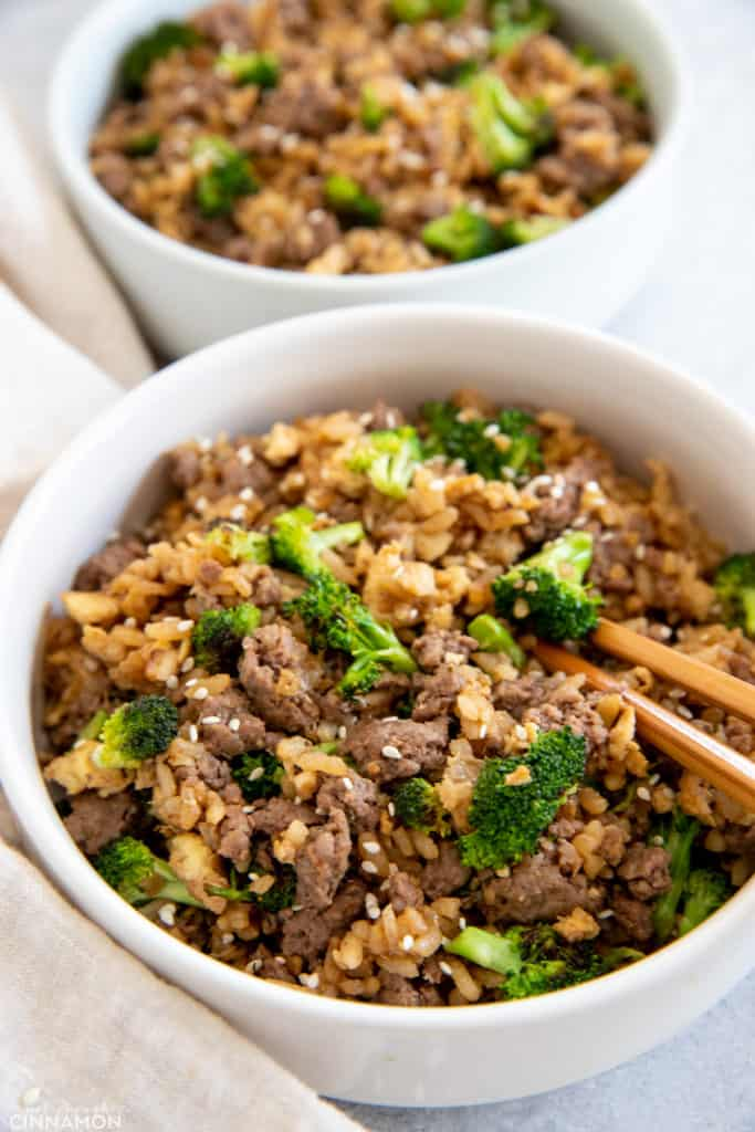 side view of beef and broccoli fried rice with chopsticks on the side