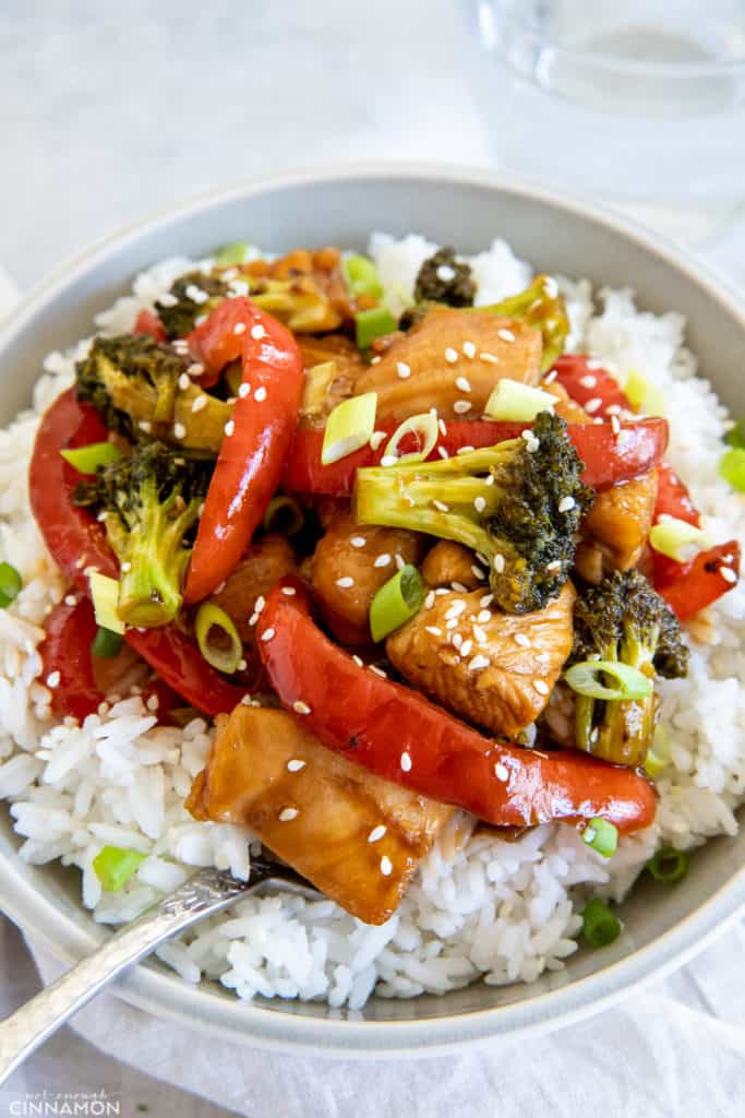 healthy hot honey chicken stir-fry with broccoli and pepper served over rice sprinkled with sesame seeds