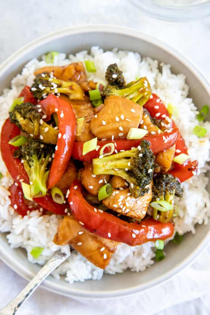 healthy hot honey chicken stirfry with bell pepper, broccoli and sweet hot honey sauce served in a bowl over rice