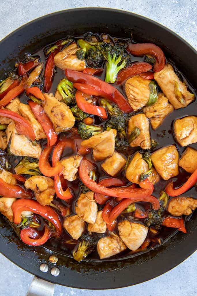 chicken breast, broccoli and red bell pepper tossed in a frying pan with hot honey frying sauce