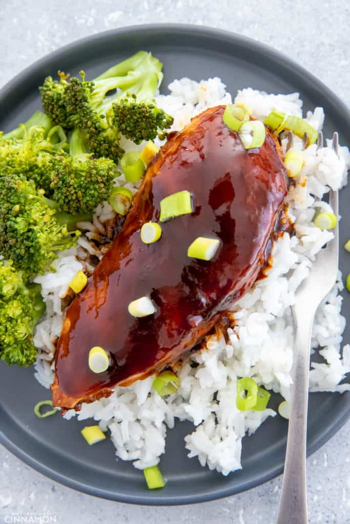 overhead shot of baked Chinese Firecracker Chicken served over rice with a side of steamed broccoli