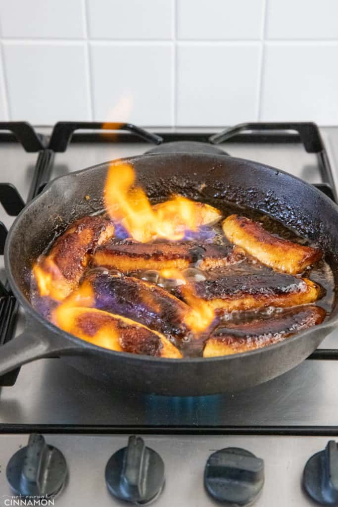 banana foster being lit on fire in a black skillet