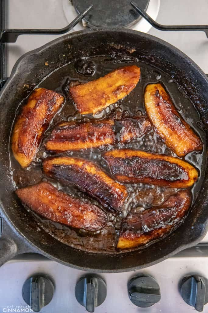 overhead shot of a black skillet with caramelized bananas in rum caramel sauce