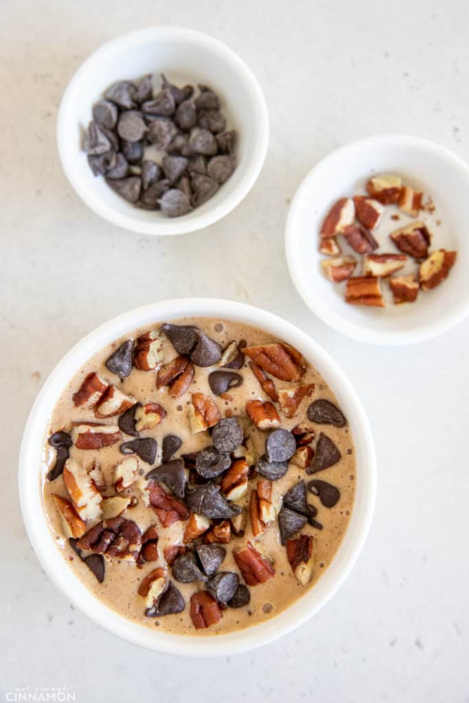 Tiktok blended baked oats batter in a small ramekin being topped with chopped pecans and chocolate chips