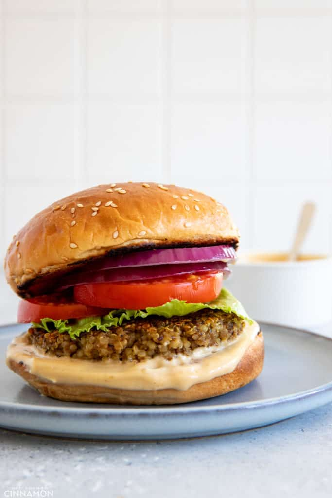 side view of a glutenfree mushroom quinoa burger with tomatoes, lettuce and homemade miso aioli