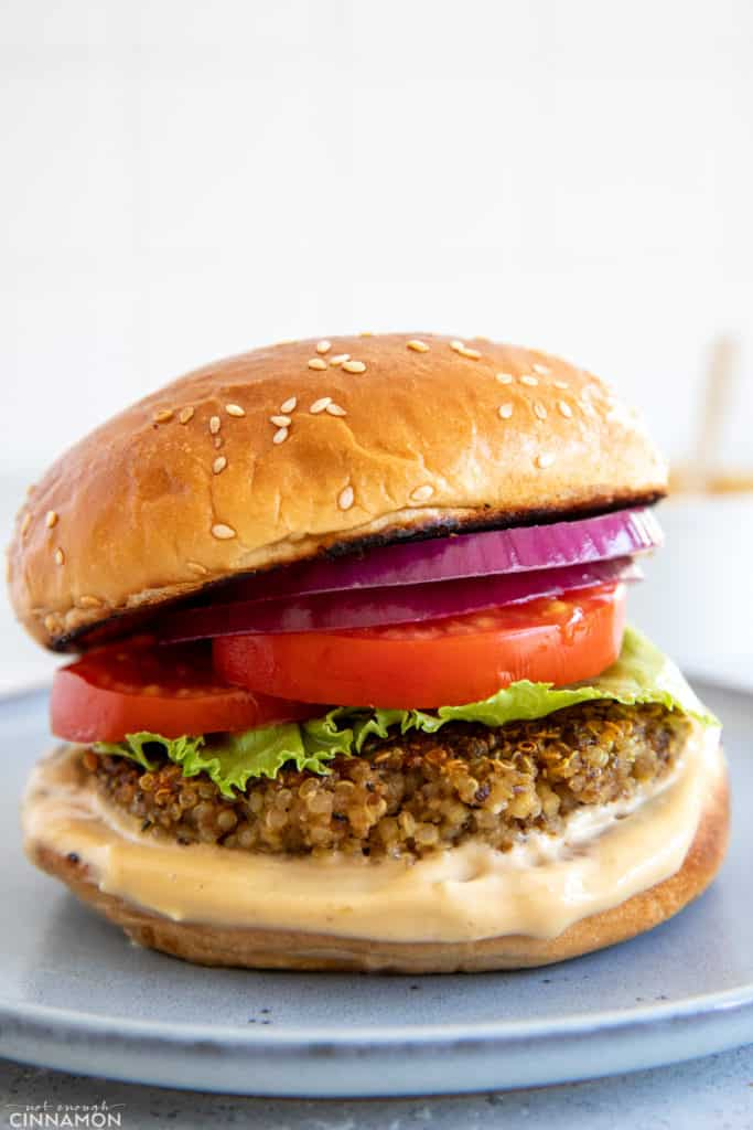 Shiitake Mushroom Quinoa Burger patty served in a burger bun with tomato onion and lettuce as well as a miso aioli